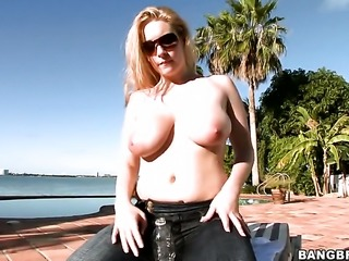 Busty blonde is playing with her tits