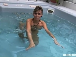 Attractive blonde milf Milly Moris shows off her huge tits in the pool