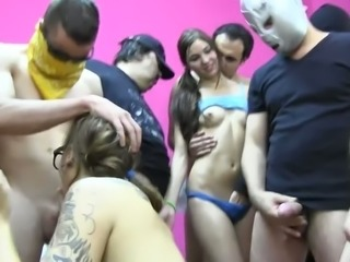 Two pretty teens with pigtails give eager blowjob to a group of dudes