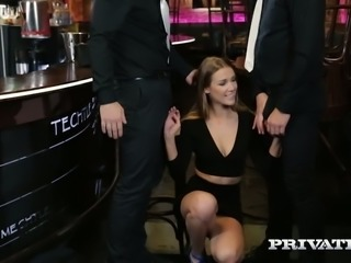 Lovely and young blonde babe at the bar blows two big dicks