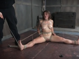 Tess has been tied with her legs spread wide and clamps attached to her...