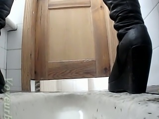 White lady in black leather boots pisses in the toilet room on cam