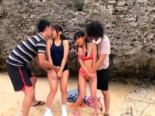 Two desirable Asian teens get rammed together on the beach